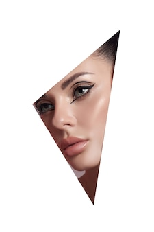 Beauty makeup women, eye brows eyelashes and lips in a triangular hole paper white background. professional beauty makeup, place for text, copy space