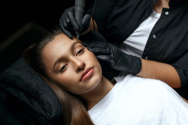 Мастер красоты наносит перманентный макияж бровей в салоне красоты. снимок крупным планом