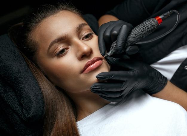 Beauty master applying lip permanent ink