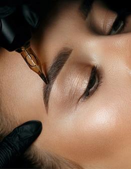 Мастер красоты, наносящий женщине перманентный макияж бровей