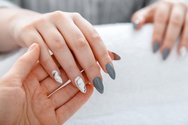 Мастер маникюра делает маникюр клиенту крупным планом акриловые искусственные ногти, окрашенные в серый и мраморный дизайн во время процедуры маникюра в салоне красоты, дизайн женских ногтей на белом полотенце