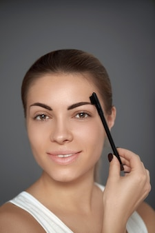 Beauty model. correcting and contouring eyebrows. beautiful woman shaping brows with comb.