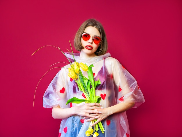 Beauty model woman in raincoat with spring flower bunch. beautiful girl with a bouquet of yellow tulip flowers. happy surprised model woman smelling flowers. mother's day gift. valentine's day.
