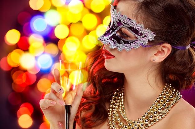 魔法の輝きと休日の暗い背景の上のパーティーでベネチアン仮面舞踏会のカーニバルマスクを身に着けている美容モデルの女性。クリスマスと新年のお祝い。完璧なメイクと髪型のグラマーレディ