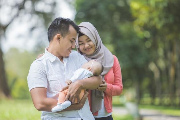 公園で生まれたばかりの赤ちゃんを持つ父親と母親