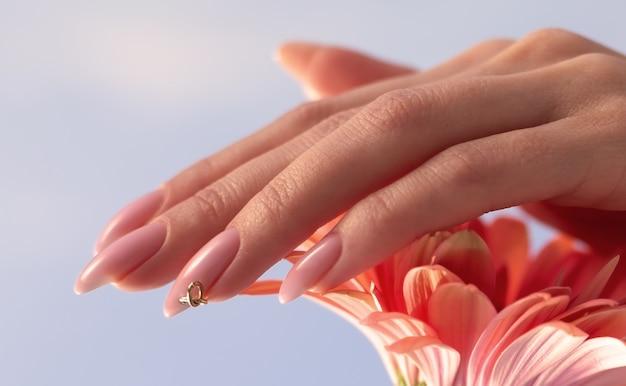Косметический уход за ногтями. нежные руки с маникюром, держа розовые лепестки крупным планом. красивые ногти крупным планом, отличная идея для рекламы косметики