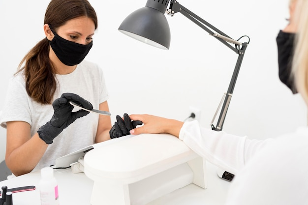 Beauty nail worker wearing face mask and gloves