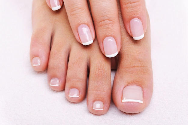 아름다운 프랑스 매니큐어와 페디큐어와 여성의 손과 발의 아름다움 손톱 개념