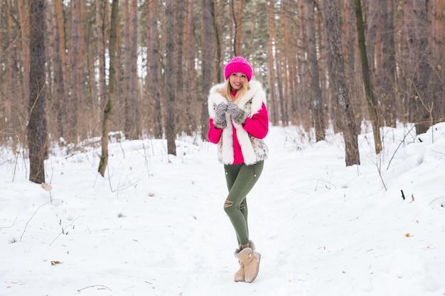 美しさ、自然、人々の概念-冬にピンクの帽子とセーターを歩く美しいブロンドの女性