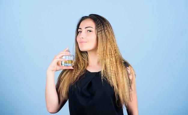 美しさは決して眠りません。セクシーな女の子は香水を保持します。トイレの水。香水のボトルを持つ女性。香水を塗る女の子。香水広告。化粧品ケア。スプレーボトルの香りの水ケルン。