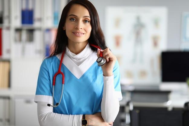 Beauty nurse in blue scrubs against clinic medical office