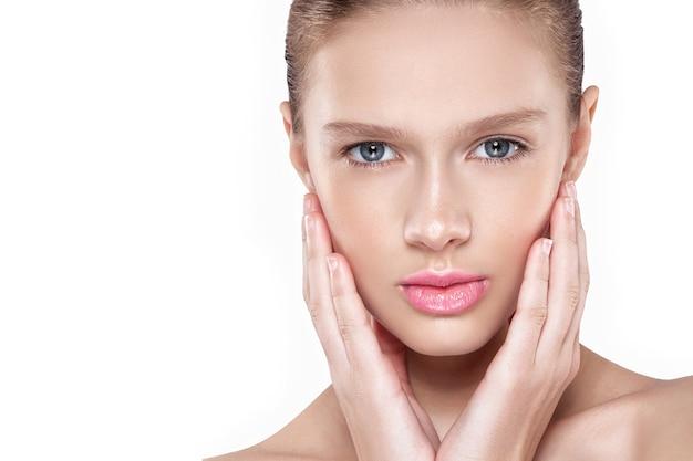 女性の顔の美しさ。ナチュラルメイク、ピンクの唇、きれいな肌。孤立した白い背景。
