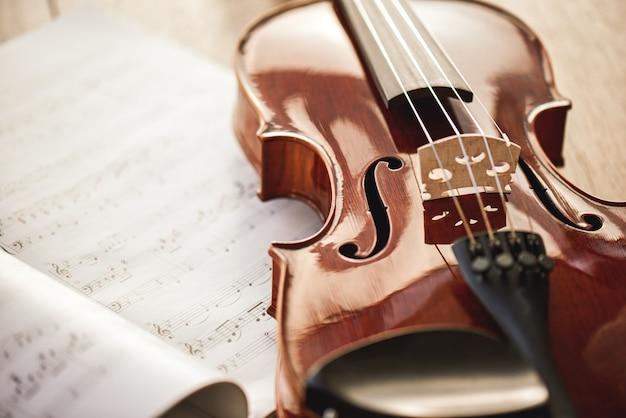 Красота музыкальных инструментов. крупным планом вид коричневой скрипки, лежащей на листах с нотами на деревянном полу. уроки игры на скрипке. музыкальные инструменты. музыкальное оборудование.