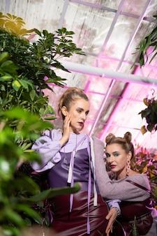 自然の美しさ。写真のポーズをしながら緑の植物の中にいるスタイリッシュな魅力的な女性