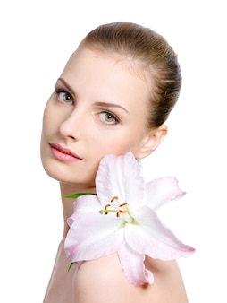 白で隔離される-肩にユリを持つ若い女性の美しさ