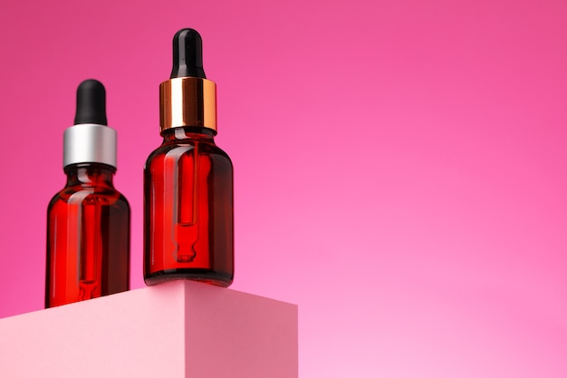 Бутылка косметического масла с пипеткой на розовом фоне