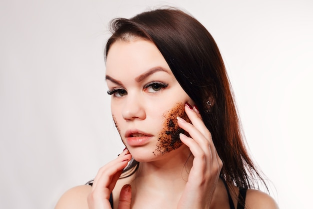 美しさ、人々、健康な肌のコンセプト-ブルネットは肌のコーヒースクラブ白い背景の美しさの肖像画を浄化します。彼女の顔に触れる美しいスパの女性。完璧なフレッシュスキンユースとスキンケアコンセプト