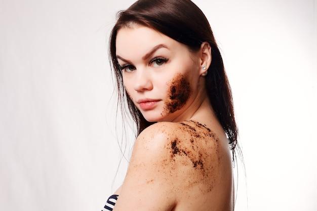 美しさ、人々、健康な肌のコンセプト-ブルネットの女性は、分離されたボディコーヒースクラブ白い背景の肌をきれいにします。美しさの肖像画。彼女の顔に触れる美しいスパの女性。完璧なフレッシュスキン。