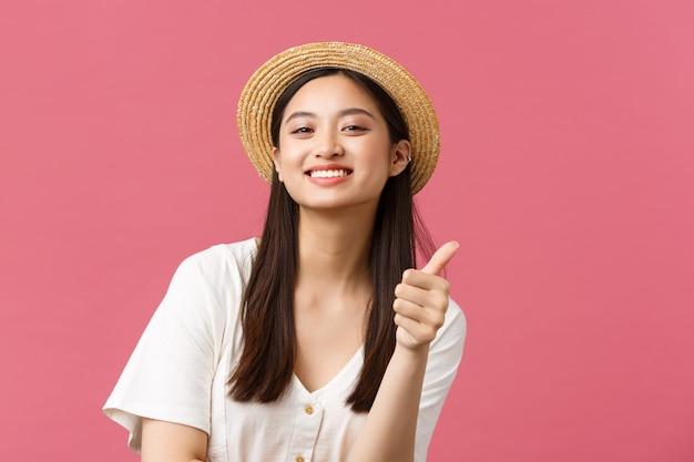 Красота, эмоции людей и концепция досуга и отдыха. крупный план довольной симпатичной азиатской покупательницы, предлагающей шикарный магазин с летней одеждой, показывая большие пальцы руки, надев соломенную шляпу.