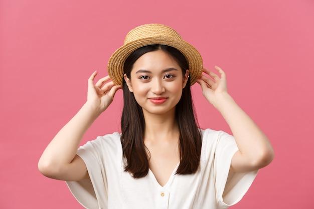 Красота, эмоции людей и концепция досуга и отдыха. прекрасная азиатская женщина делает покупки в магазине, выбирает новую соломенную шляпу, радостно улыбается, покупает летнюю одежду на розовом фоне.