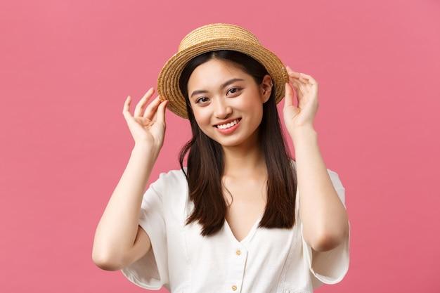아름다움, 사람들의 감정, 레저 및 휴가 개념. 사랑스러운 아시아 여성이 가게에서 쇼핑하고, 새 밀짚 모자를 고르고, 기뻐하며 웃고, 분홍색 배경 위에 여름 옷을 사고 있습니다.