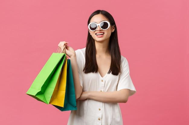 아름다움, 사람들의 감정, 여름 레저 및 휴가 개념. 휴가 중 평온한 행복한 아시아 소녀, 쇼핑백을 들고 선글라스를 착용한 관광객, 만족스러운 분홍색 배경 미소.