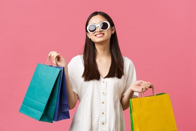 美しさ、人々の感情、夏のレジャーと休暇のコンセプト。休暇中ののんきな幸せなアジアの女の子、買い物袋を持ってサングラスをかけている観光客、満足のいく笑顔、ピンクの背景。