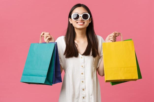 Красота, эмоции людей и концепция летнего отдыха и отпуска. беззаботная счастливая азиатская девушка в отпуске, турист, держащий хозяйственные сумки и в солнцезащитных очках, удовлетворенный улыбкой, розовый фон.