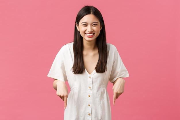 아름다움, 사람들의 감정, 여름 레저 및 휴가 개념. 하얀 드레스를 입은 평온하고 나가는 귀여운 아시아 소녀는 기쁨에 웃고, 손가락을 아래로 가리키고, 파티나 행사에 초대합니다.