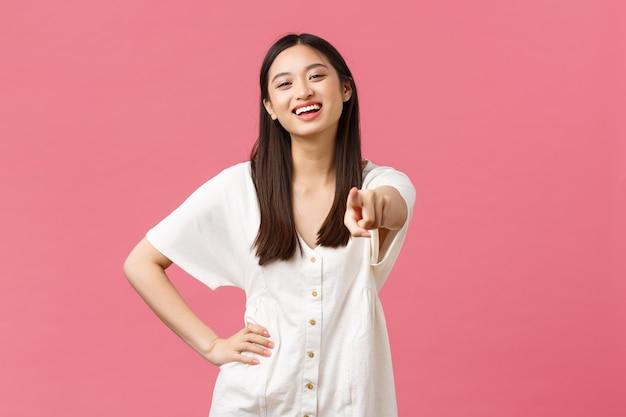 美しさ、人々の感情、夏のレジャーと休暇のコンセプト。カメラを指して、顧客を招待し、あなたを選び、祝福し、または訪問店を奨励する陽気な熱狂的なアジアの女の子。