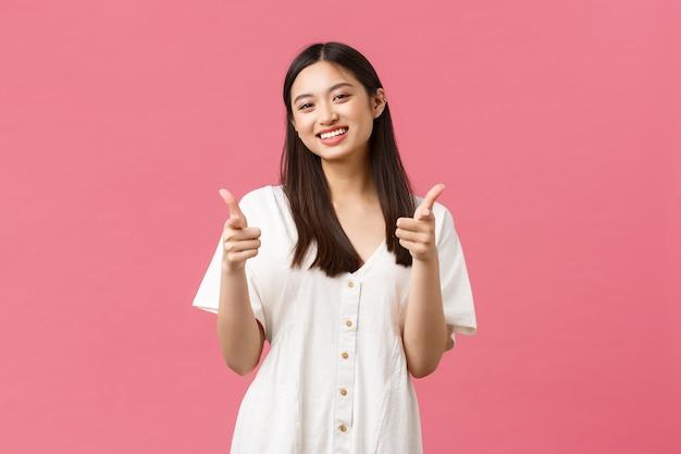 Красота, эмоции людей и концепция летнего отдыха и отпуска. веселая глупая корейская девушка в белом платье показывает большие пальцы руки и улыбается, улыбается довольна, довольна продуктом, рекомендую