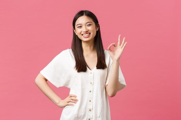 Красота, эмоции людей и концепция летнего отдыха и отпуска. уверенная, жизнерадостная азиатская девушка без проблем показывает все хорошие жесты и глупо подмигивает, поощряет посещение магазина, розовый фон.