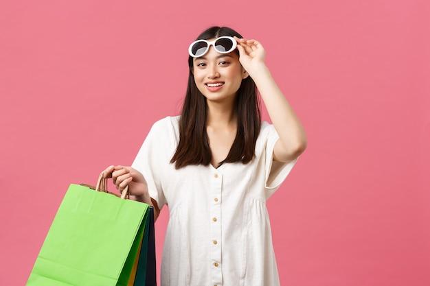 Красота, эмоции людей и концепция летнего отдыха и отпуска. красивая гламурная азиатская девушка снимает очки и улыбается в камеру с хозяйственными сумками, наслаждаясь выходным днем в торговом центре.