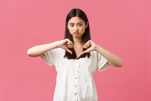 美しさ、人々の感情、夏のレジャーと休暇のコンセプト。判断力のある不機嫌で懐疑的なかわいいアジアの女の子はがっかりし、嫌いなピンクの背景で親指を下に見せています。