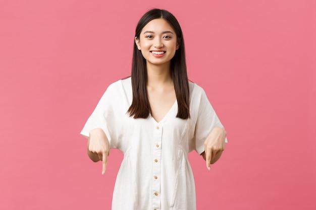 Красота, эмоции людей и концепция летнего отдыха и отпуска. гордая счастливая и довольная азиатская девушка в белом платье, приглашая проверить специальное предложение в магазине, указывая пальцами вниз, розовый фон.