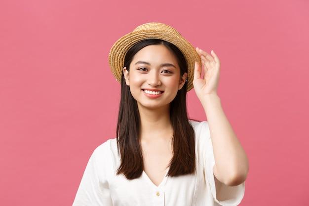 美しさ、人々の感情、夏のレジャーと休暇のコンセプト。麦わら帽子とかわいい白いドレスのスタイリッシュでファッショナブルなアジアの女の子がカメラに微笑んで、ショッピング、ピンクの背景を楽しんでいます。