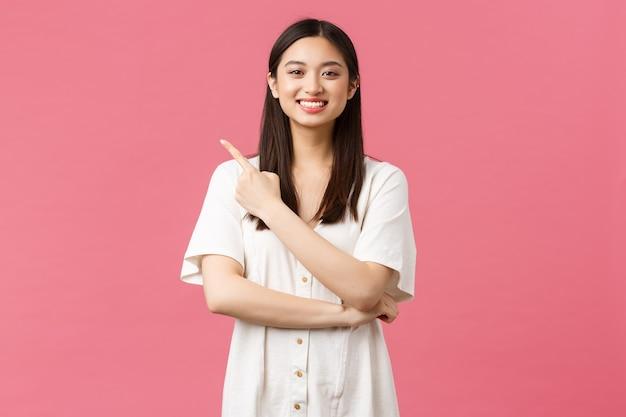아름다움, 사람들의 감정, 여름 레저 개념. 분홍색 배경 위에 왼쪽 상단 모서리 광고를 가리키며 카메라를 향해 미소를 짓고 있는 드레스를 입은 아름다운 열정적인 아시아 여성.