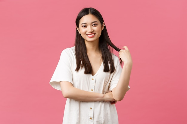 Красота, эмоции людей и концепция летнего отдыха. беззаботная милая корейская девушка в белом платье, улыбающаяся и трогательная прядь волос мечтательным счастливым взглядом, стоящая на розовом фоне