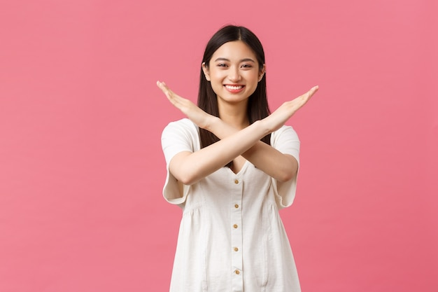 Красота, эмоции людей и концепция летнего отдыха. веселая улыбающаяся азиатская девушка вежливо просит остановиться, показать крест, знак запрета и запрета, улыбаясь счастливым, стоя на розовом фоне.