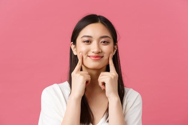 美しさ、人々の感情、夏のレジャーのコンセプト。かわいいディンプル、頬に触れ、幸せな笑顔、立っているピンクの背景を持つ面白いとかわいいアジアの女性のクローズアップ。