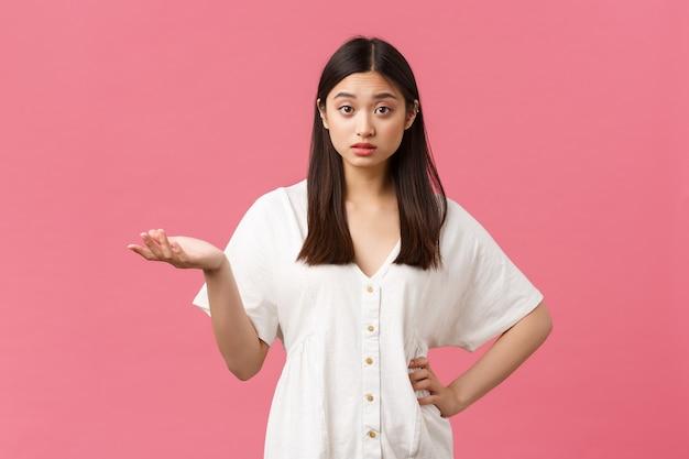 아름다움, 사람들의 감정, 여름 레저 개념. 흰색 드레스를 입은 혼란스럽고 어리둥절한 아시아 소녀, 손을 들고 어깨를 으쓱하고, 분홍색 배경을 원하는 것을 이해할 수 없습니다.