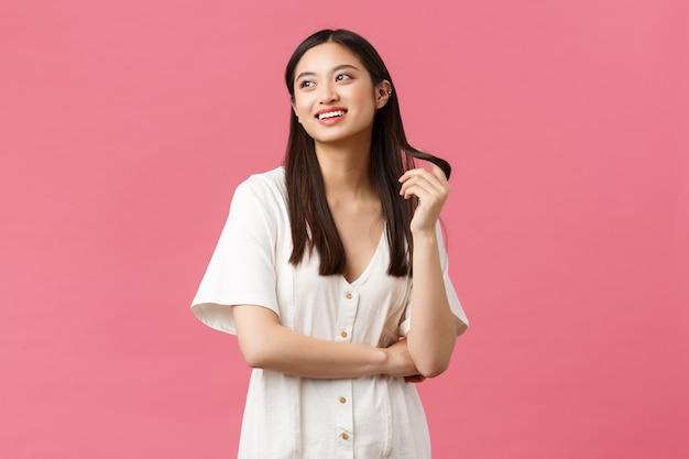 Красота, эмоции людей и концепция летнего отдыха. мечтательная азиатская девушка в белом платье изображает что-то с глупой улыбкой, играет с прядью волос и смотрит в левый верхний угол, белый фон.