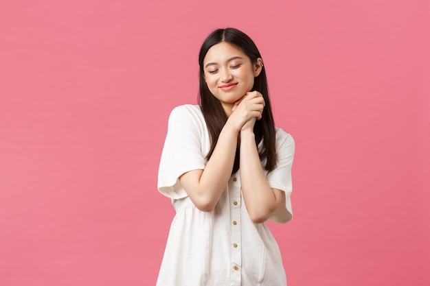 아름다움, 사람들의 감정, 여름 레저 개념. 꿈꾸고 낭만적인 아시아 소녀는 얼굴에 손을 꼭 잡고 웃고, 무언가를 상상하고, 분홍색 배경을 상상하는 아름다운 기억을 기억합니다.