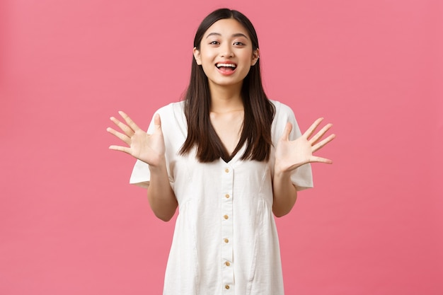 美しさ、人々の感情、夏のレジャーのコンセプト。興奮した魅力のかわいいアジアの女の子は、大きな発表、ピンクの背景を伝えるように、素晴らしいニュース、身振り、手を上げる、笑顔を説明します。