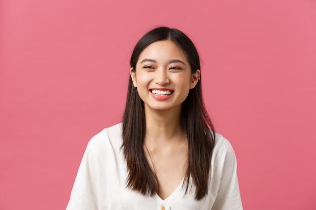 아름다움, 사람들의 감정, 여름 레저 개념. 즐겁고 평온하게 웃고 있는 아시아 여성은 여름을 즐기고, 분홍색 배경에 서서, 활기차게 웃고, 긍정적인 분위기를 가지고 있습니다.