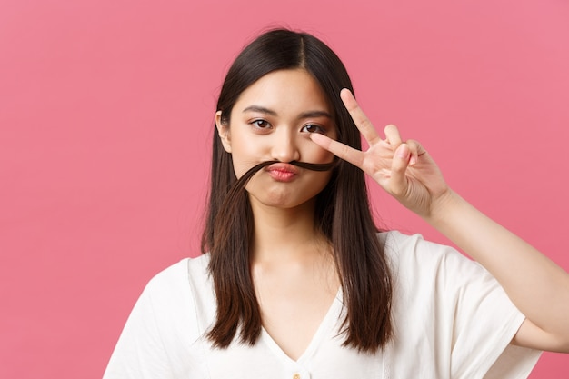 아름다움, 사람들의 감정, 여름 레저 개념. 장난스럽고 어리석은 아시아 소녀는 평화 기호를 보여주고 콧수염, 분홍색 배경처럼 입술 위에 머리카락을 잡고 장난을 칩니다.