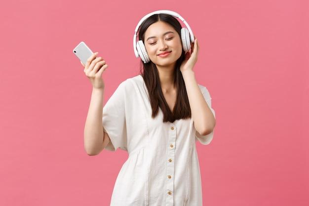 Красота, эмоции людей и концепция технологии. беззаботная и симпатичная азиатская девушка наслаждается музыкой в беспроводных наушниках, закрывает глаза и улыбается, слушает любимую песню, держит смартфон и танцует.