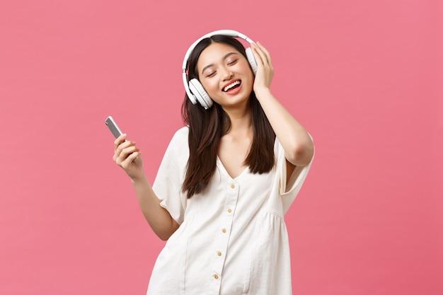 美しさ、人々の感情と技術の概念。のんきでかわいいアジアの女の子は、ワイヤレスヘッドフォンで音楽を楽しんだり、目を閉じたり、お気に入りの曲を聴いたり、スマートフォンを持って踊ったりして笑っています。