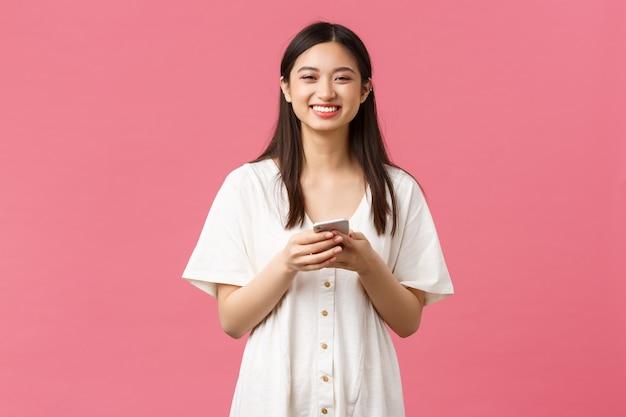 Красота, эмоции людей и концепция технологии. веселая гламурная азиатская девушка с помощью мобильного телефона, улыбка на камеру и обмен сообщениями, текстовые сообщения друзьям. blogger, использующий приложение для социальных сетей.