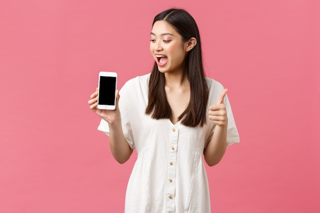 Красота, эмоции людей и концепция технологии. возбужденная счастливая азиатская девушка, блогер демонстрирует потрясающее приложение, показывая экран мобильного телефона и большие пальцы руки на розовом фоне.
